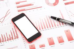 Blank mobile phone  on red graphs, charts , data and business report summariz Stock Photos