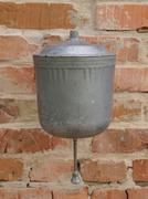 old metal water dispenser basin on a brick wall. - stock photo