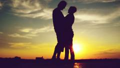 Lovers on a date in sunset, hugging and kissing. Romantic love scene Stock Footage