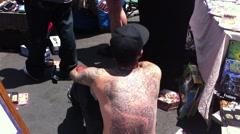 Bloody man inside crime tape stabbing flea market Stock Footage