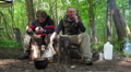 Two tourists , man, have dinner in  wood Footage