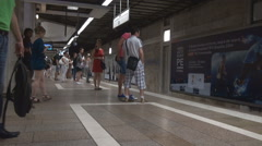 Inside subway station, subway train coming in station fast, commuters waiting Stock Footage