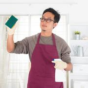 Stock Photo of asian man doing house chores