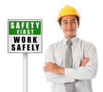 asian male wearing yellow hardhat with safety first sign board. - stock photo
