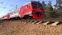 Red-gray suburban train of RZD (russian railway) rides to the forest. Stock Footage