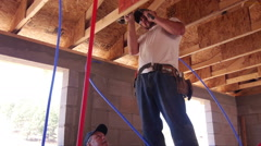 Construction worker wiring a light fixture Stock Footage