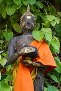 thai monk statue in temple holding alms bowl - stock photo