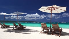 Sun umbrellas and beach chairs on coastline with white sand - stock footage