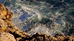 Blue water waves and a rocky beach Stock Footage