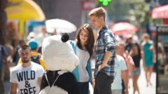 4K & HD resolutions: Lovers stand above the crowd stream with the big toy bear Stock Footage