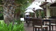 Thailand Pattaya 002 ravindra beach resort terrace with sunshades and palm trees Stock Footage