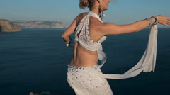 Oriental dancer performing a dance on one of the mountains near  sea in Crimea Stock Footage