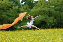 agile woman leaping in the air trailing a scarf - stock photo