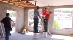 Construction worker putting up drywall Stock Footage
