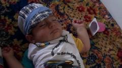 Sleeping baby and empty yoghurt can Stock Footage