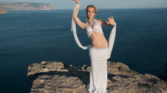 Beautiful girl shows all the beauty of oriental dance standing on a mountain in Stock Footage