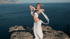 Stunner girl shows all the beauty of oriental dance standing on a mountain in Stock Footage