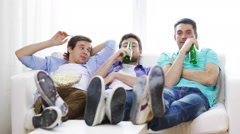 Male friends with beer watching tv at home Stock Footage