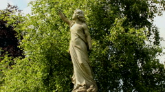 Monumental, statue of a woman without hands on a background of green tree. Stock Footage