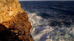 Colorful cliff line with deep blue ocean and breaking waves Stock Footage