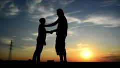 Man meeting woman on the street in sunset and greeting her with a warm handshake Stock Footage