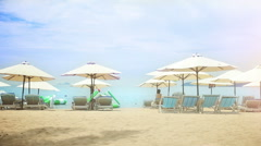 Sun umbrellas and chairs on a sandy beach. Stock Footage