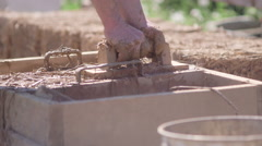 Forming clay and hay brick Stock Footage