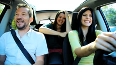 Two beautiful women and one handsome man having fun driving car happy - stock footage