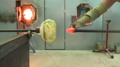 Glass artist attaches base on vase - stock footage