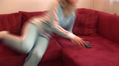 Stock Video Footage of HD1080 Young blonde woman lying on couch and looking tv. Version 7