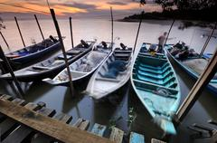 Fisherman docks floating on water at sunset - stock photo