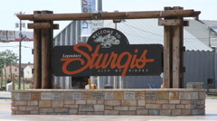 Sturgis city limits sign with biker going by Stock Footage
