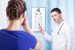 Oculist examining patient Stock Photos