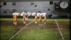 1129 - cheerleaders on football field at half-time - vintage film home movie Stock Footage