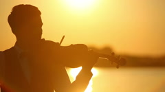 Male violinist playing the violin at the lake at sunset Stock Footage
