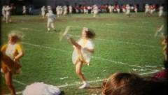 1126 - high kicking cheerleaders at the football game - vintage film home movie - stock footage