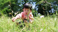 Japanese young boy playing with magnifying glass in a park, Tokyo, Japan - stock footage