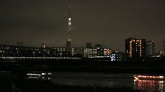 Boats cruising on Arakawa river at night and Tokyo Skytree, Tokyo, Japan Stock Footage