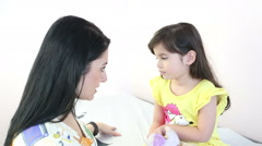 Beautiful therapist preparing a little girl to give a massage Stock Footage