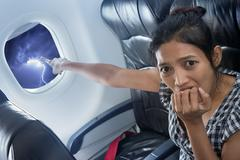 Woman inside airplane shows the lightning in the sky Stock Photos