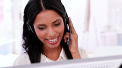 Call centre agent working and talking on headset - stock footage