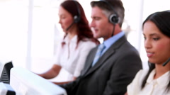 Call centre agents working and talking on headsets - stock footage