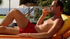 Happy man drinking cocktail on sunbed, lying on sunbed by luxury villa HD Stock Footage
