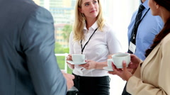 Business people standing at conference drinking coffee - stock footage