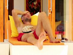 Sad, bored young handsome man lying on sunbed by luxury villa NTSC Stock Footage