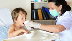 Kid eating and drinking under doctor observation Stock Footage