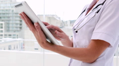 Nurse in tunic using tablet pc and smiling at camera Stock Footage