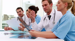 Medical team looking at xray and files during meeting Stock Footage