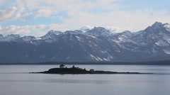 Aerial shot of small Alaskan island - house, snowy mountains background Stock Footage