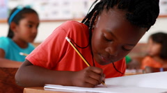 Little girl writing and smiling at camera during class Stock Footage